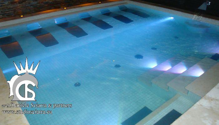 La piscina con i lettini idromassaggio, le sedute e le cascate per idroterapia